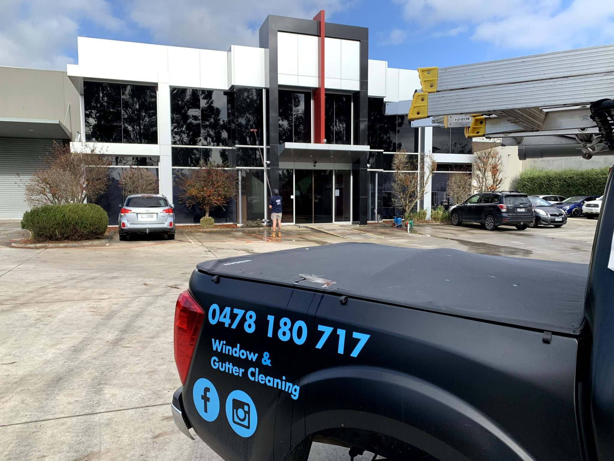 Window and Gutter Cleaning business has a sign written car parked in front of a commercial building in the Yarra Valley